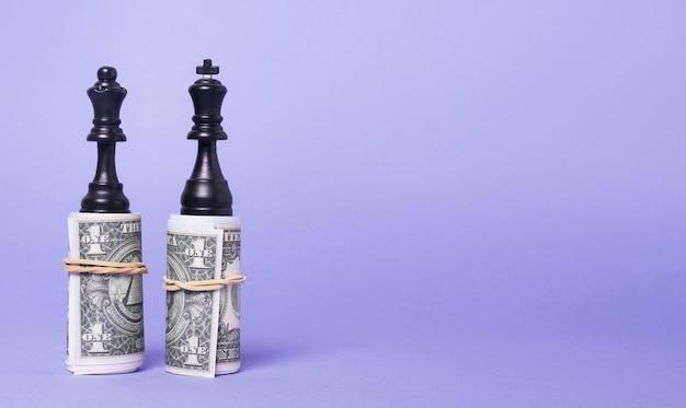 Koning en koningin stukken van schaak staande op geld met kopie ruimte