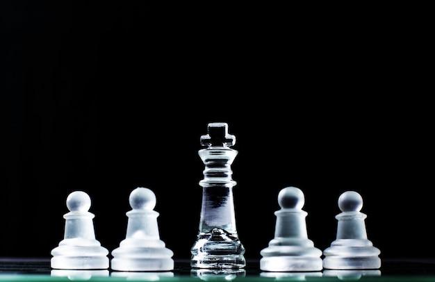 Koning en meerdere pionnen op schaakbord op donkere achtergrond. hiërarchieconcept.