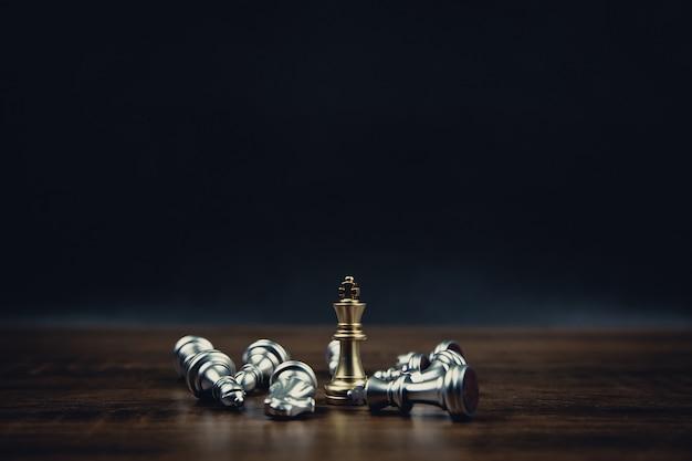 Koning gouden schaken staande van het vallende zilveren schaakspel met donkere achtergrond.