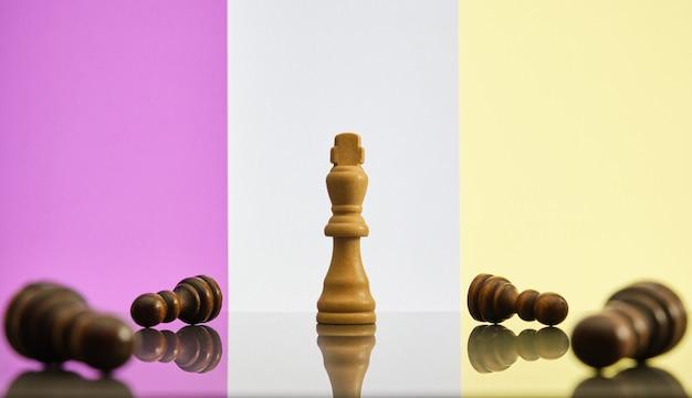 Koning is het laatste schaakstuk dat staat, omgeven door zwarte gevallen pionnen. doorzettingsvermogen, immuniteit en veerkracht concept.