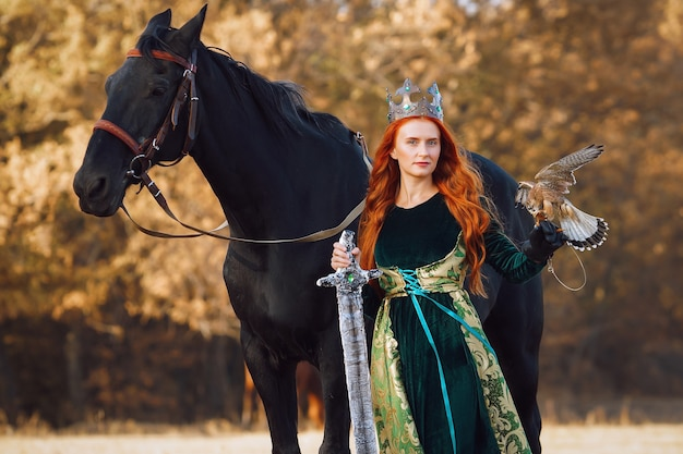 Koningin met rood haar in een groene jurk met een kroon en een zwaard bij een paard met een vogel