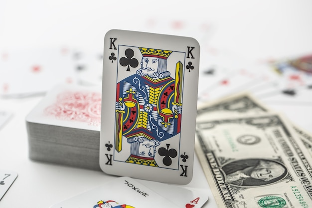 Koningskaart met stapel andere kaarten naast een dollarbankbiljetten.