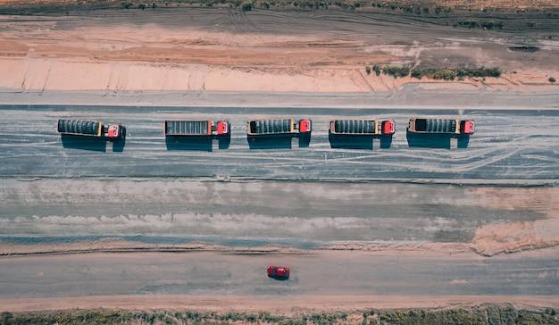 Konvooi van vrachtwagens beweegt langs asfaltweg bedekt met zand bovenaanzicht
