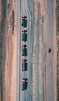 Konvooi van vrachtwagens rijden op asfaltweg met een rode auto aan de andere kant van de weg
