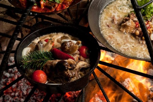 Kook een vleesgerecht met sparren takken op de brandstapel