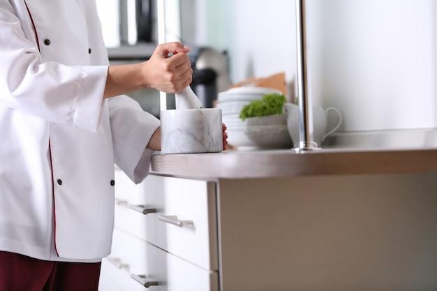 Kook handen met vijzel met kruiden