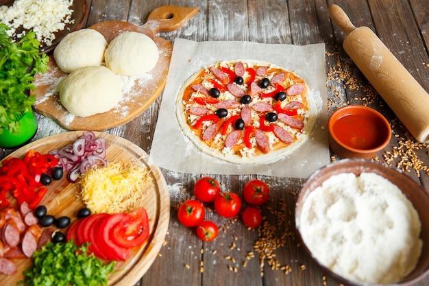 Kook in de keuken en leg de ingrediënten op de pizza