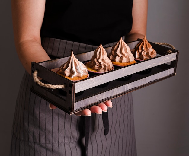 Kook met dienblad met cakejes en glazuur