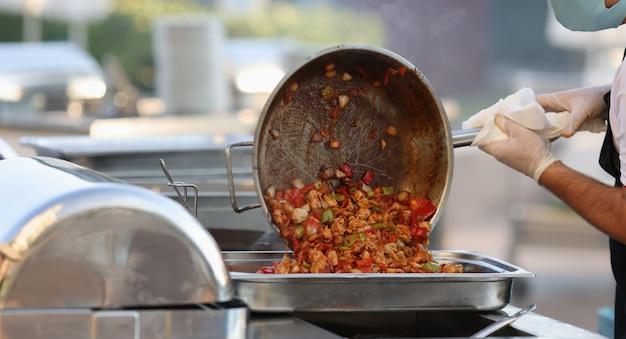 Kook met een beschermend masker en bak groenten in de pan