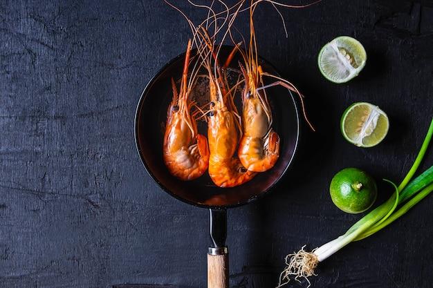 Kook zeevruchtengarnalen in een pan.
