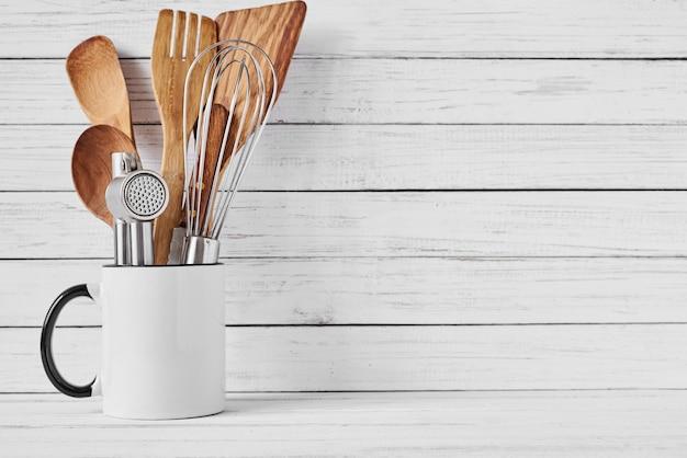 Kookhulpmiddelen in ceramische kop met copyspace