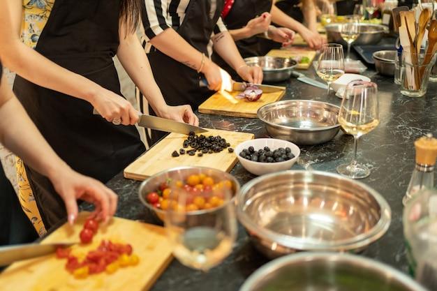 Kookles, culinair, voedsel en mensenconcept, groep vrienden die in keuken koken