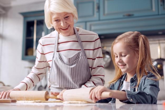 Kooklessen. charmant klein meisje dat naast haar grootmoeder staat en samen met haar deeg uitrolt, in navolging van haar voorbeeld