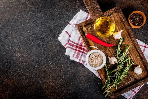 Kookoppervlak, kruiden, zout, specerijen, olijfolie op snijplank, donker roestig oppervlak bovenaanzicht