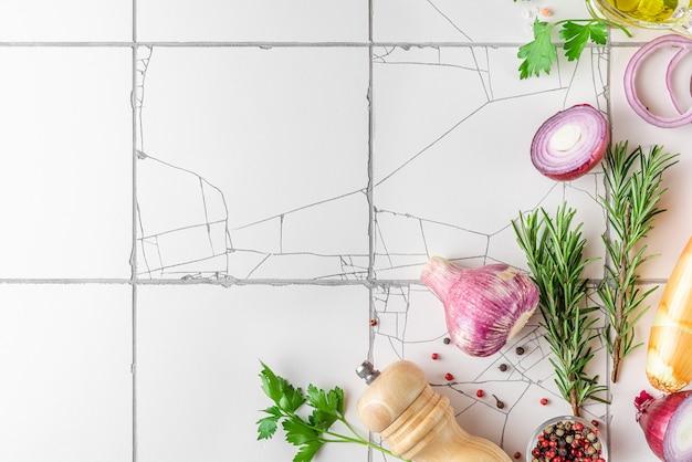 Kookoppervlak met specerijen, kruiden en groenten op witte rustieke tegeltafel