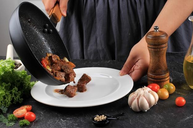 Kookproces, aziatische vrouw chef-kok zet gegrilde wagyu fatty saikoro cubed dobbelstenen biefstuk met barbecue saus op zwarte pan naar witte plaat