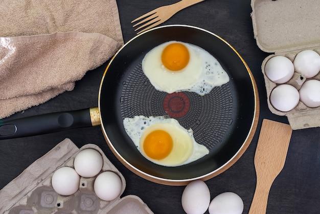 Kookproces van gebakken eieren. twee gebakken eieren in een pan en rauwe eieren op een donkere houten.
