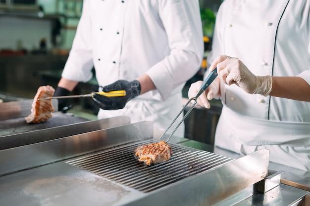 Kookt gebraden vlees op het fornuis in de keuken van een restaurant of hotel.