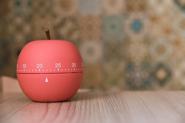 Kookwekker in de vorm van een appel op een zonnige keuken op tafel, aftellend tweeëntwintig minuten