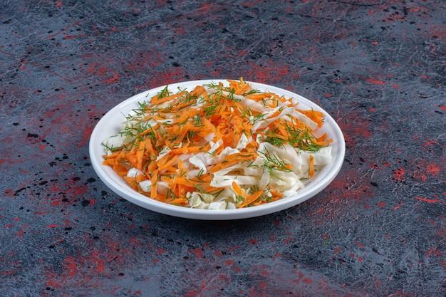Kool en wortelsalade op een schotel op zwarte lijst.