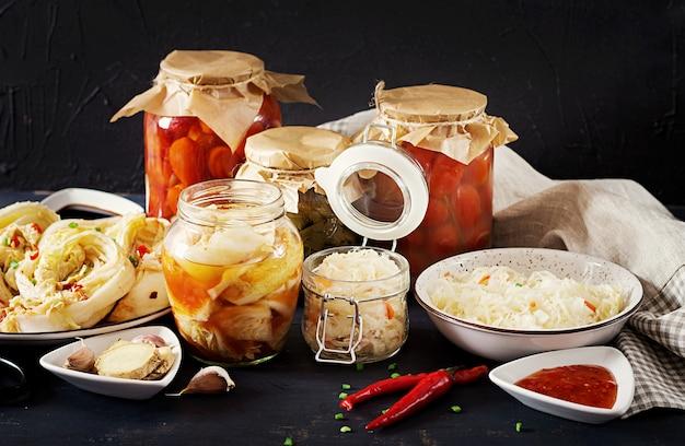 Kool kimchi, gemarineerde tomaten, zuurkool zuurkool potten over rustieke keukentafel.