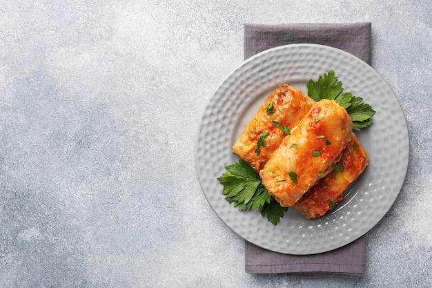 Koolbroodjes met rundvlees, rijst en groenten op de plaat. gevulde koolbladeren met vlees. grijze betonnen tafel exemplaarruimte.
