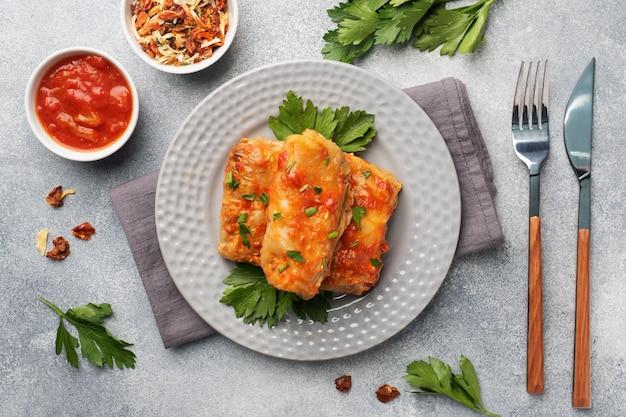 Koolbroodjes met rundvlees, rijst en groenten op de plaat. gevulde koolbladeren met vlees. grijze betonnen tafel
