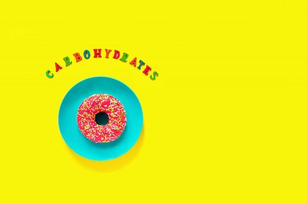 Koolhydraten en roze donut op blauw bord op gele achtergrond.
