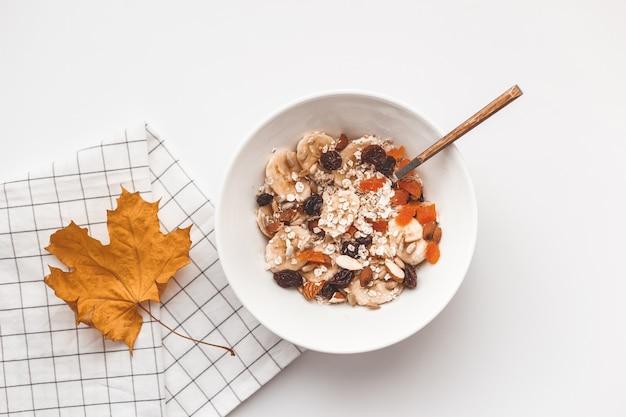 Koolhydraten gezond ontbijt. havermout met gedroogde vruchten op een witte plaat. uitzicht van boven