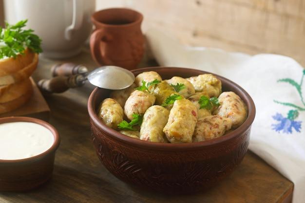 Koolrolletjes geserveerd met zure room, brood en wijn. dolma, sarma, sarmale, golubtsy of golabki.