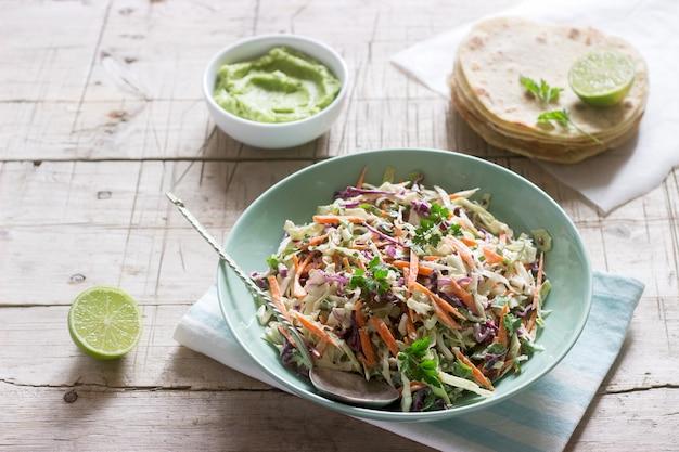 Koolsla gemaakt van kool, wortelen en diverse kruiden, geserveerd met tortilla's en guacamala op een houten ondergrond.