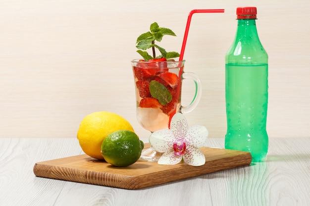 Koolzuurhoudende limonade met plakjes aardbei en munt op een houten snijplank, koude drank voor warme zomerdag