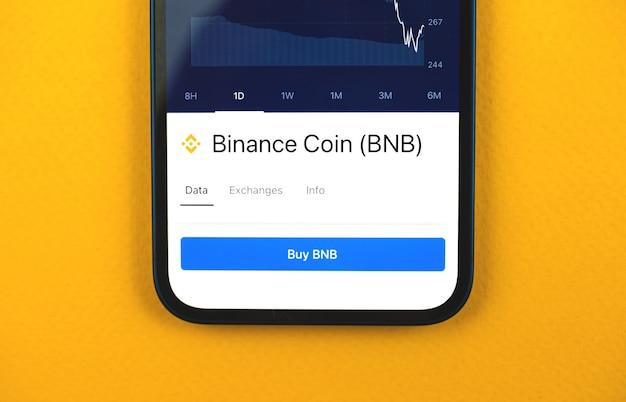 Koop binance munt bnb cryptocurrency, mobiele app met knop, concept van online handel en uitwisseling met behulp van smartphone, bankapplicatie, bovenaanzicht foto van zakelijk bureau
