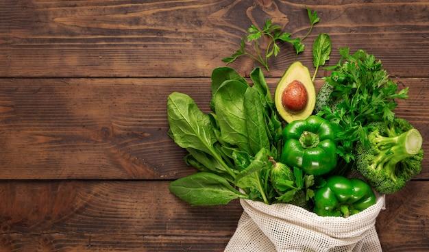 Koop gezond voedsel. bovenaanzicht boodschappentas met gezond voedsel schoon eten. groene groente op houten hoogste mening als achtergrond