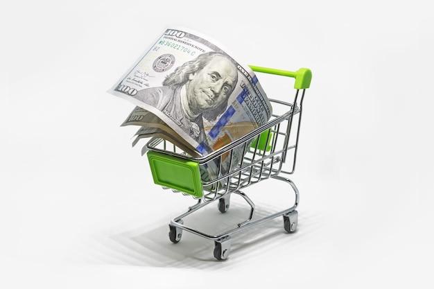 Koop vreemde valuta. aankoop van bankbiljetten 100 dollar. winkelmandje met dollar bankbiljetten, rekeningen geïsoleerd op een witte achtergrond