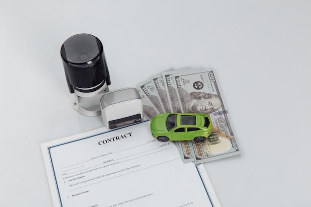 Koopcontract voor een auto met geld, postzegels en speelgoedauto.