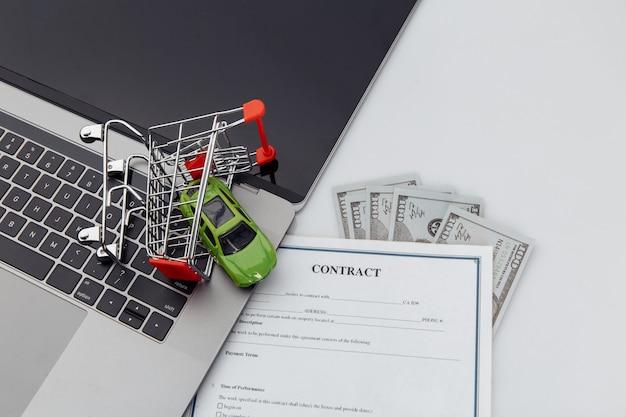 Koopcontract voor een auto met laptop en speelgoedauto in een winkelwagentje.