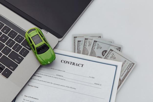 Koopcontract voor een auto met laptop en speelgoedauto.