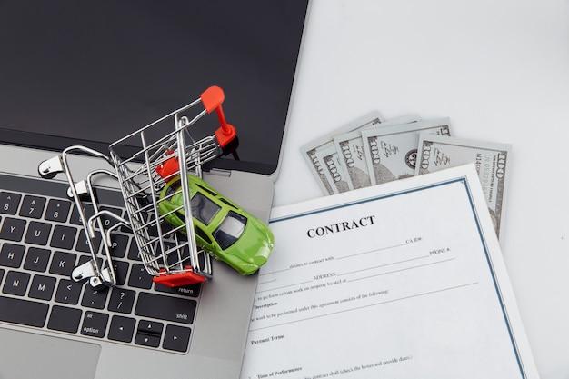 Koopcontract voor een auto met laptop, geld en speelgoedauto in een winkelwagentje.