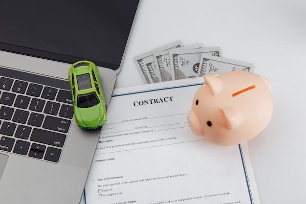 Koopcontract voor een auto met laptop, spaarvarken en speelgoedauto.
