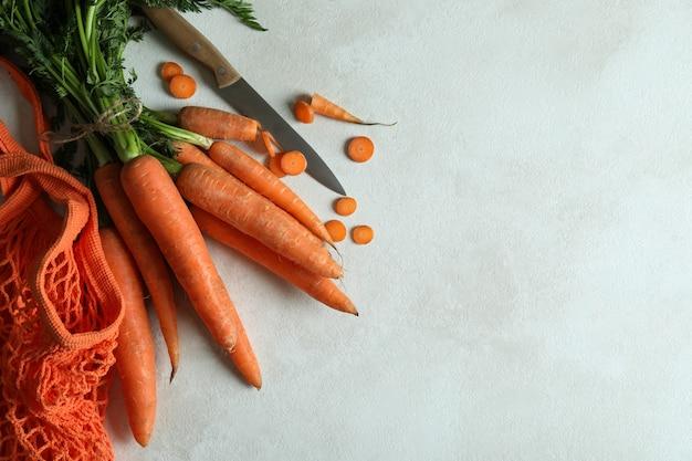 Koordzak, mes en wortel op wit gestructureerd oppervlak