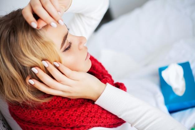 Koorts en verkoudheid. portret van mooie vrouw gevangen griep, hoofdpijn en hoge temperatuur. close-up van ziek meisje bedekt met deken, ziek gevoel houden thermometer. gezondheidszorg. hoge resolutie.