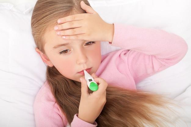 Koorts, verkoudheid en griep - medicijnen en hete thee in het nabije, zieke meisje in bed