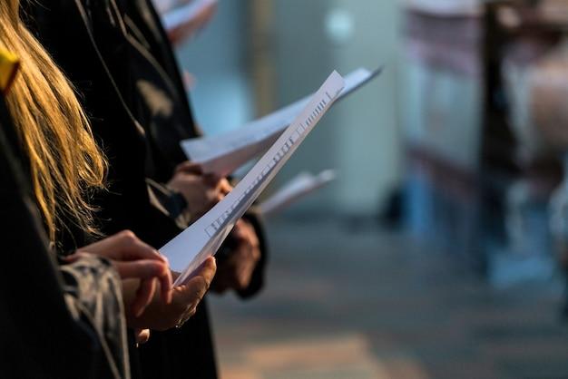 Koorzangers houden muziekscore en zingen op de afstudeerdag van de student.
