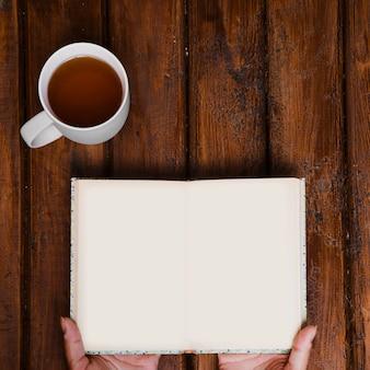 Kop aromatische thee en open boek op oud hout