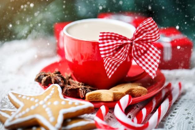 Kop cacao, koekjes, giften en sparrentakken op een witte houten lijst