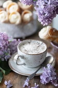 Kop cappuccino en cakekegels van bladerdeeg met vanillecrème in een metalen doos in het voorjaarstilleven met een boeket seringen op een houten tafel