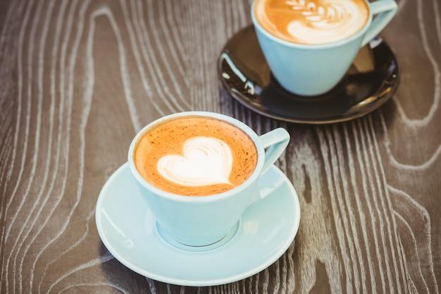 Kop cappuccino met koffiekunst op houten lijst bij koffiewinkel