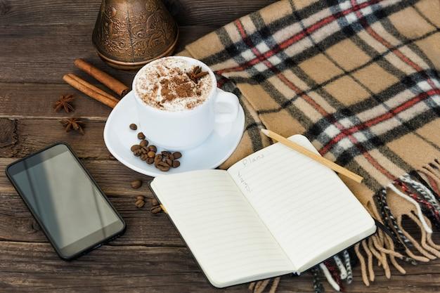 Kop cappuccino-, smartphone- en koffiepotten op een bruine houten tafel.