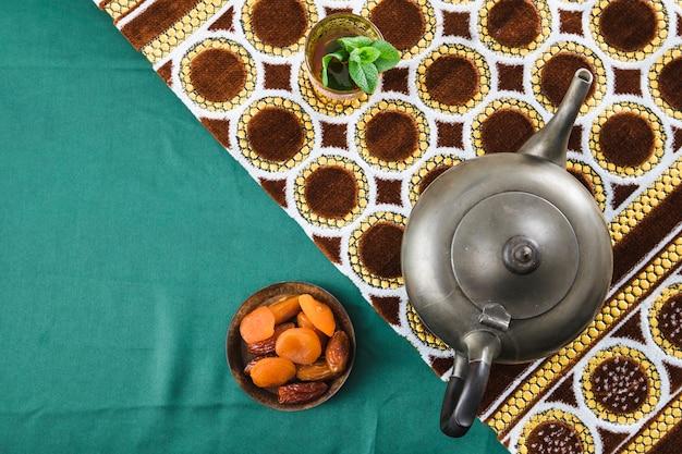 Kop dichtbij retro theepot en gedroogd fruit dichtbij mat op gerimpeld materiaal
